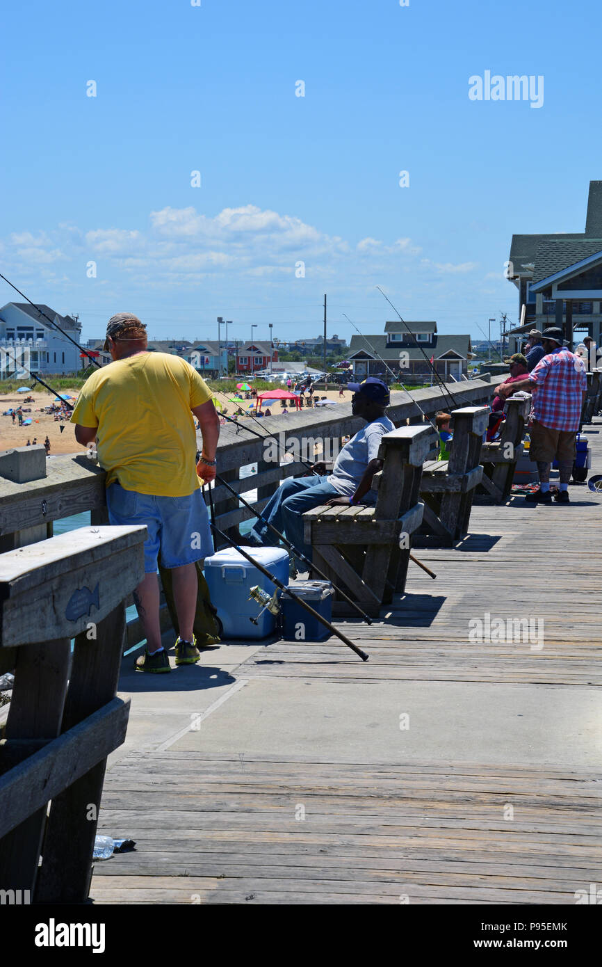 Men fishing off of Jenette's Pier in Nags Head on the Outer Banks of North Carolina - Stock Image