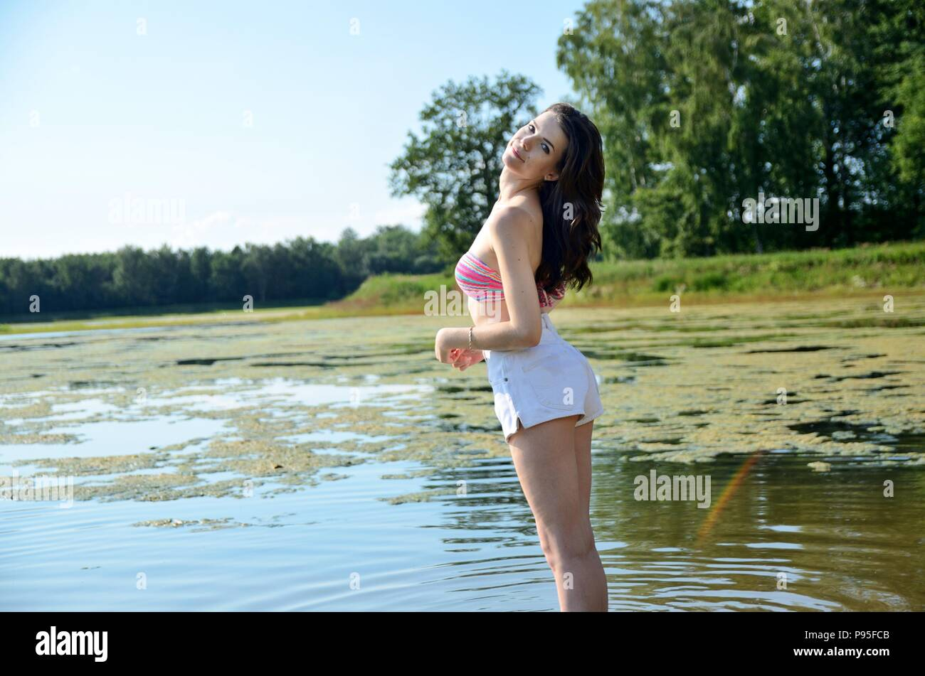 Young female model in outdoor photo session in Poland. Girl in short pants and bikini top stands in lake. Stock Photo