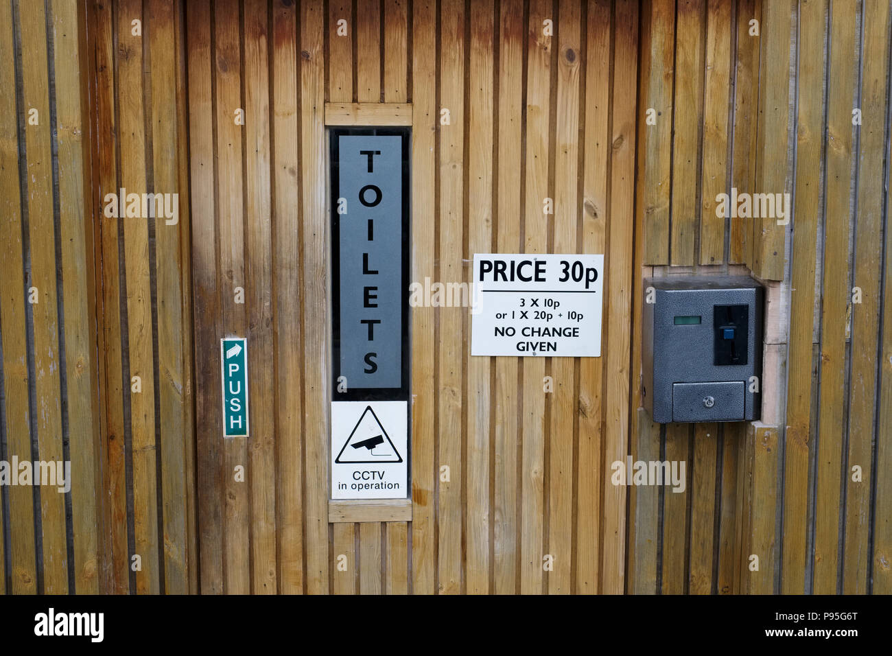 Public toilet WC coin operated pay to use in outdoor park - Stock Image