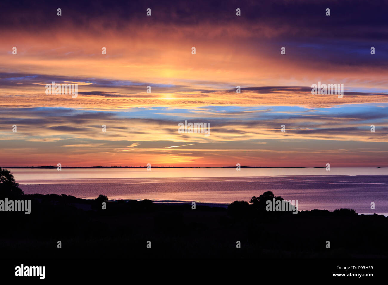 Summer sunset over Tralee Bay and the Maharees along the Wild Atlantic Way viewed from Camp on the Dingle Peninsula in County Kerry, Ireland - Stock Image
