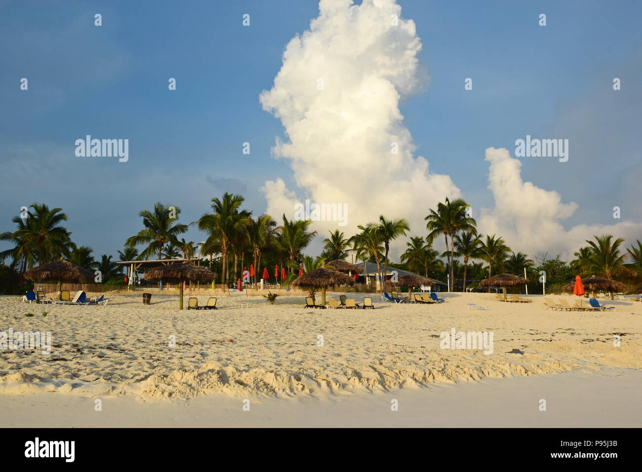 Treasure Cay beach with Coco beach bar and restaurant in backgorund.  Tiki beach umbrellas and chairs, palm trees and cumulonimbus cloud in sky. - Stock Image