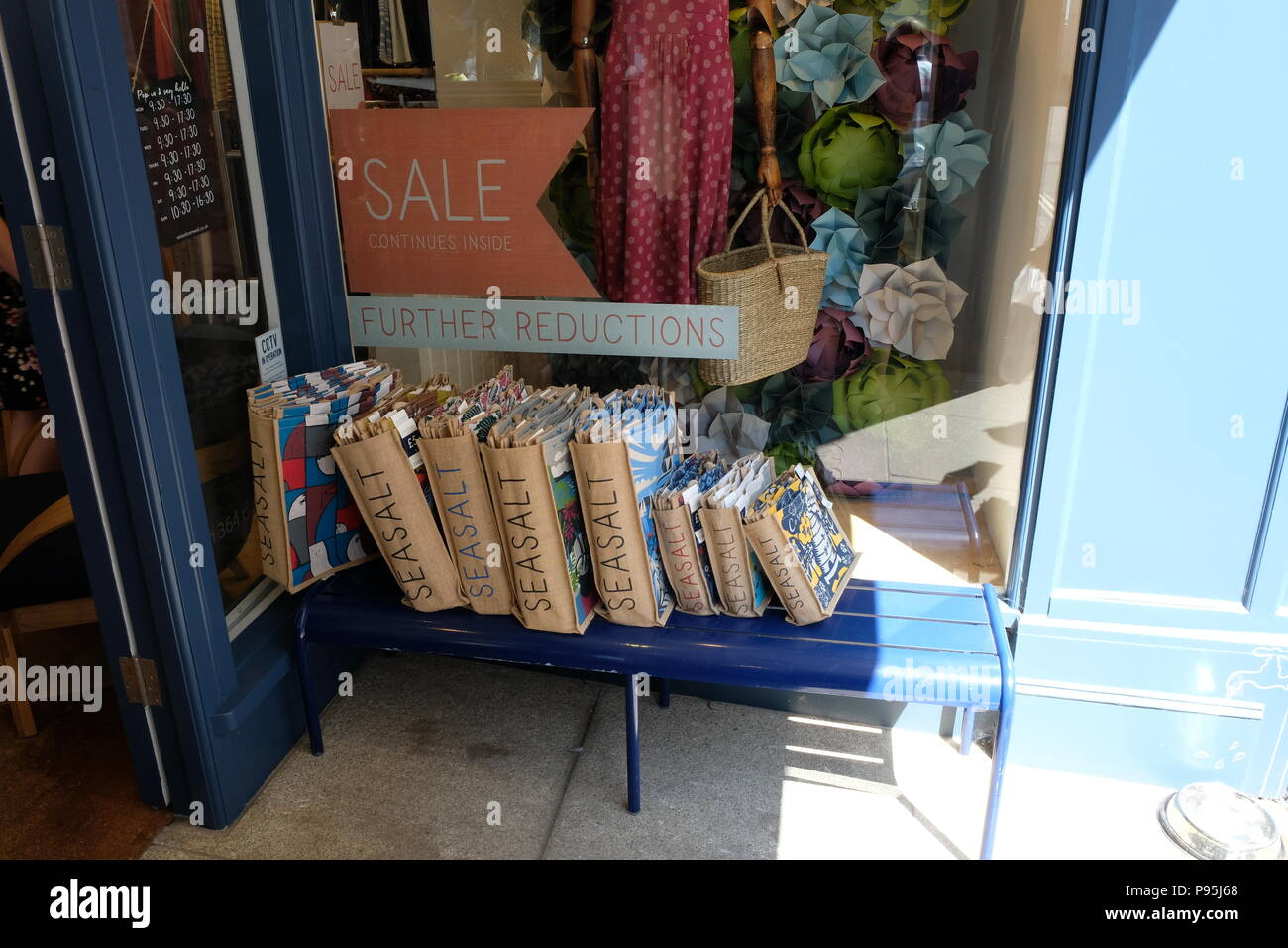 Sisal Seasalt branded shopping bags are displayed outside a Sesalt UK branch in Sidmoth, East Devon, UK - Stock Image