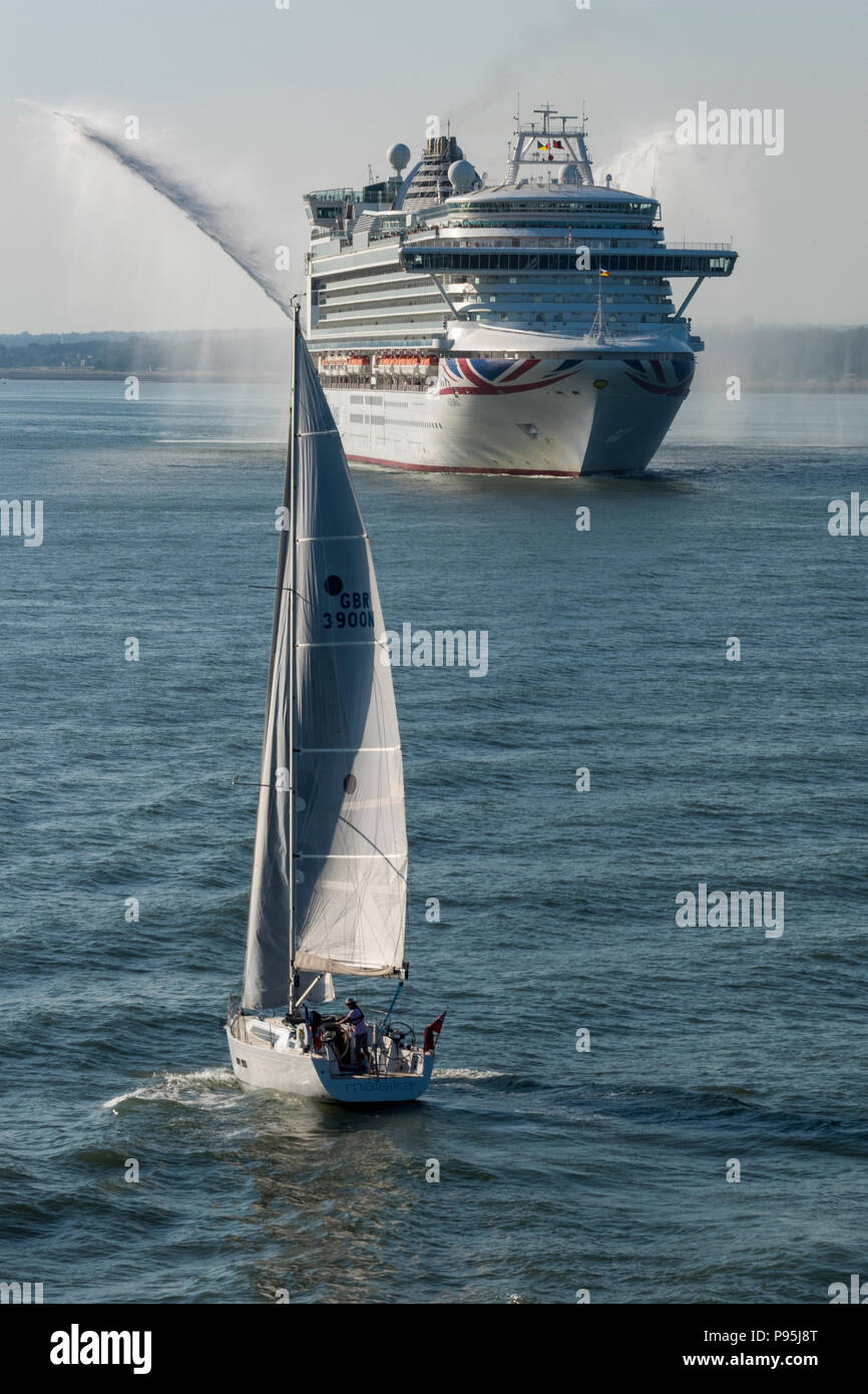 p and o cruise liner azura leaving the port of southampton with a sailing yacht in the foreground. - Stock Image