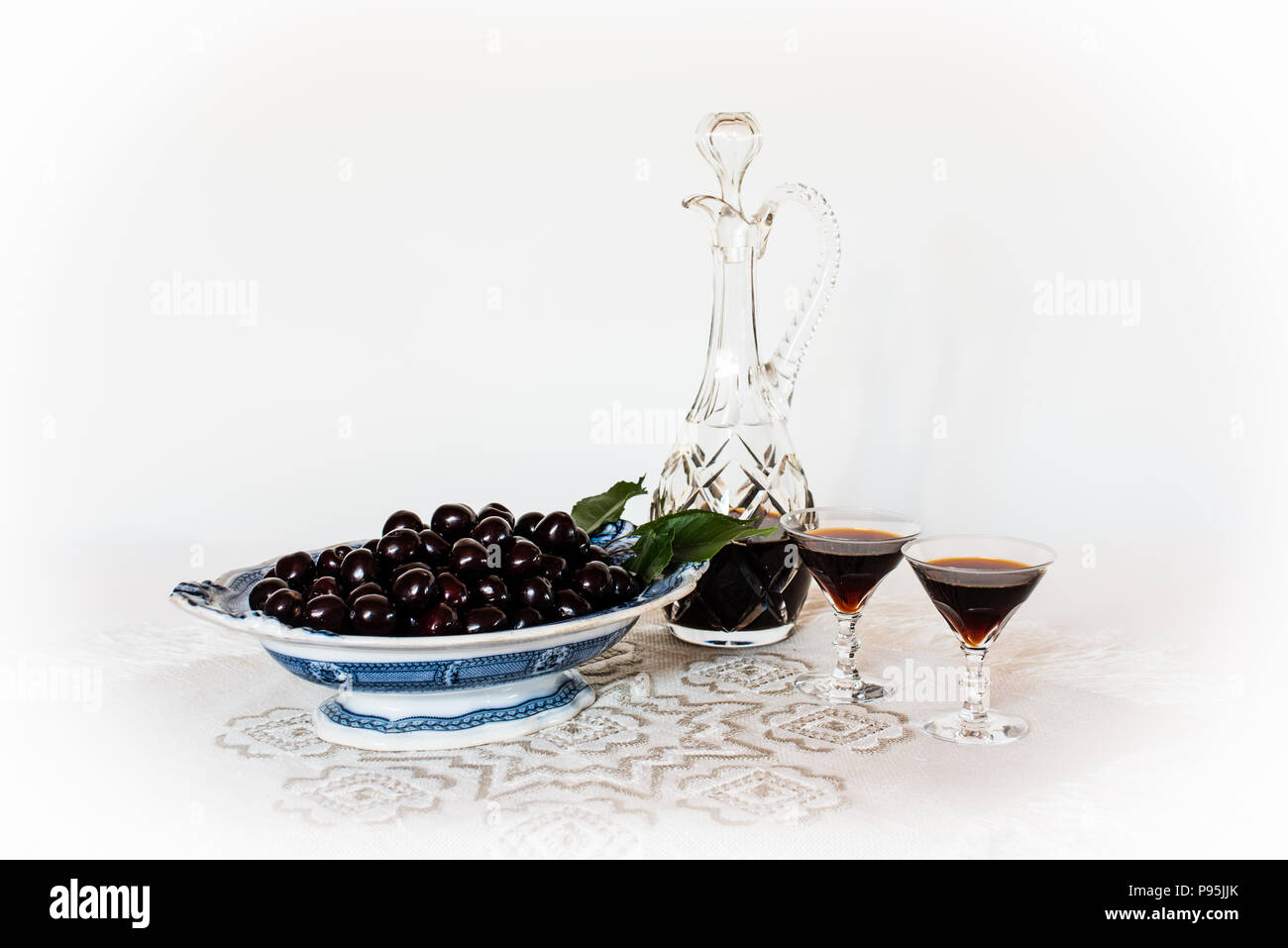Cherries on an old china dish and a crystal carafe and glasses with cherry brandy on a table cloth with a white background, a still life. - Stock Image