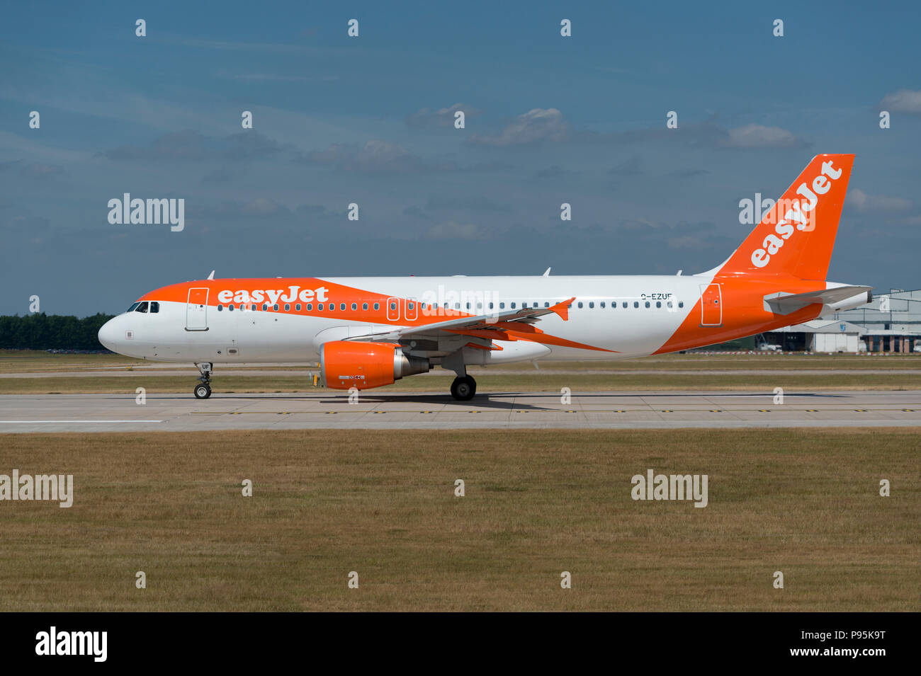 An Easyjet Airbus A319 sits on the runway at Manchester Airport as it prepares to take-off. - Stock Image