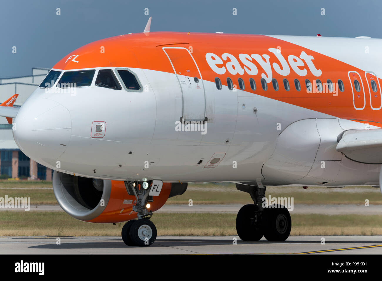 An Easyjet Airbus A319 taxis along the runway at Manchester Airport whilst preparing to take off. - Stock Image