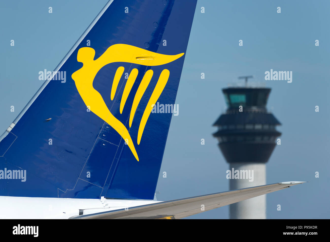 The tailfin of Ryanair Boeing 737-800 taxiing along the runway in front of the control tower at Manchester Airport. - Stock Image