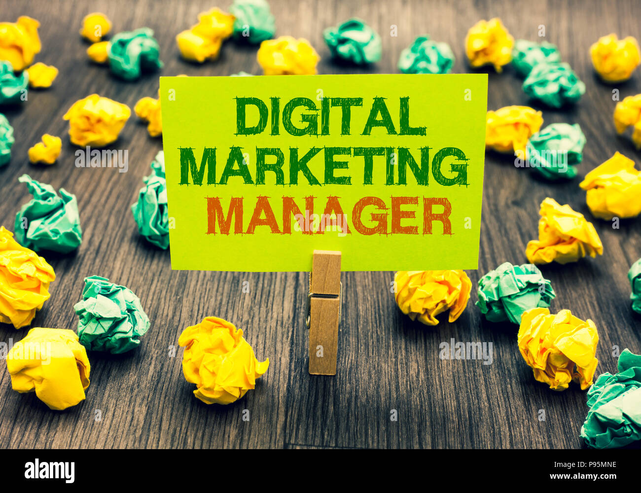 Word writing text Digital Marketing Manager. Business concept for optimized for posting in online boards or careers Clothespin holding yellow note pap - Stock Image