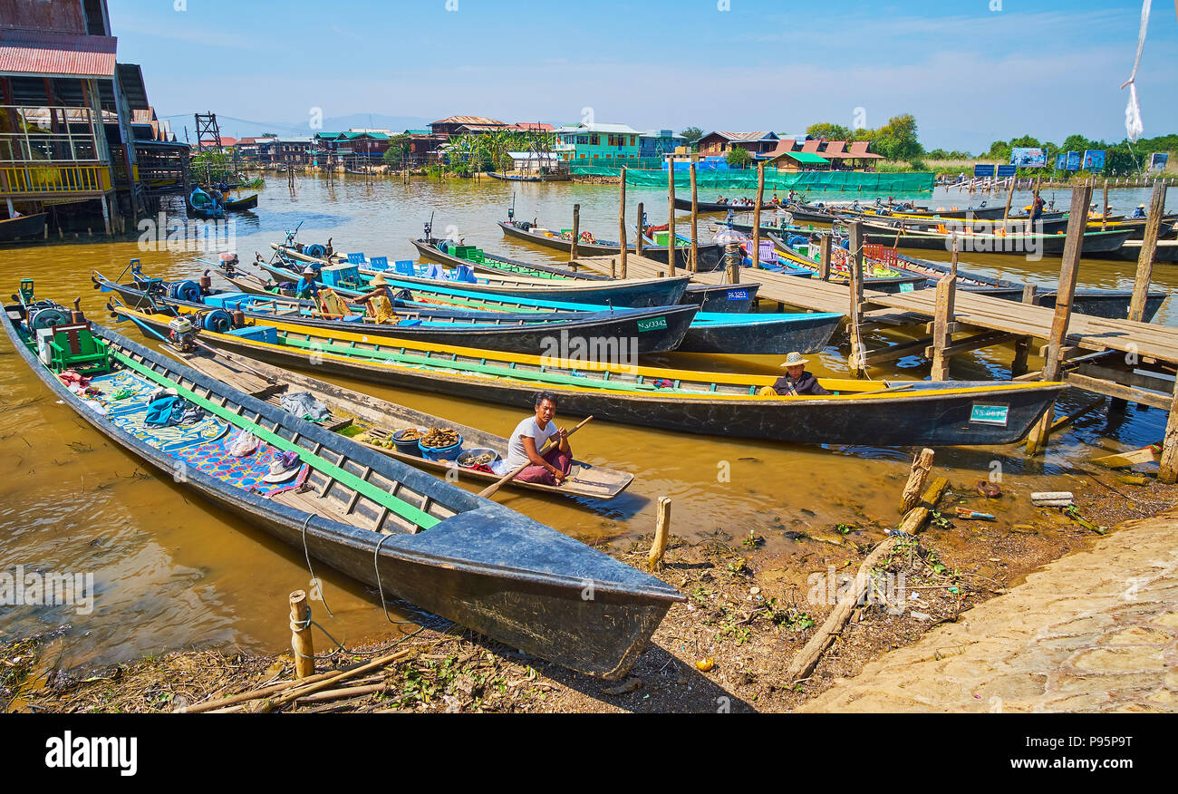 YWAMA, MYANMAR - FEBRUARY 18, 2018: The wharf with moored kayaks and the boat of the food celler, offering traditional Burmese snacks and fresh fruits - Stock Image