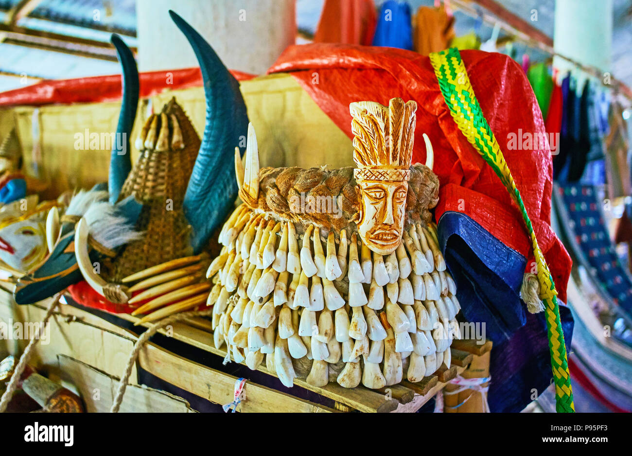 The unusual souvenir - tribal male headdress, decorated with animals' teeth, handicraft market of Inn Thein (Indein) village on Inle Lake, Myanmar. - Stock Image