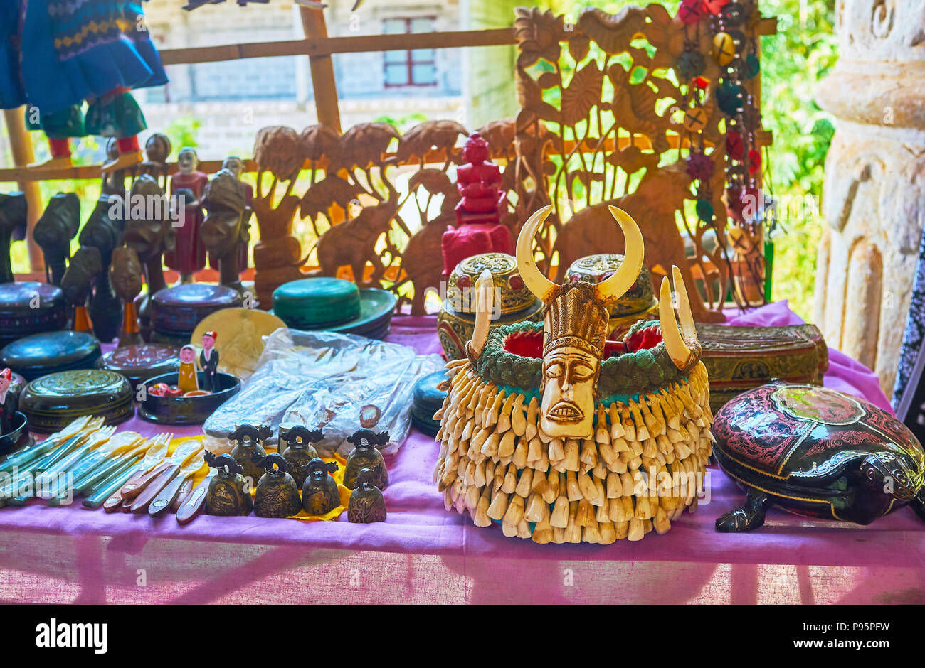 The counter of tourist stall with different souvenirs and gifts for interior design, such as wooden sculptures, bells and tribal male headdress, decor - Stock Image
