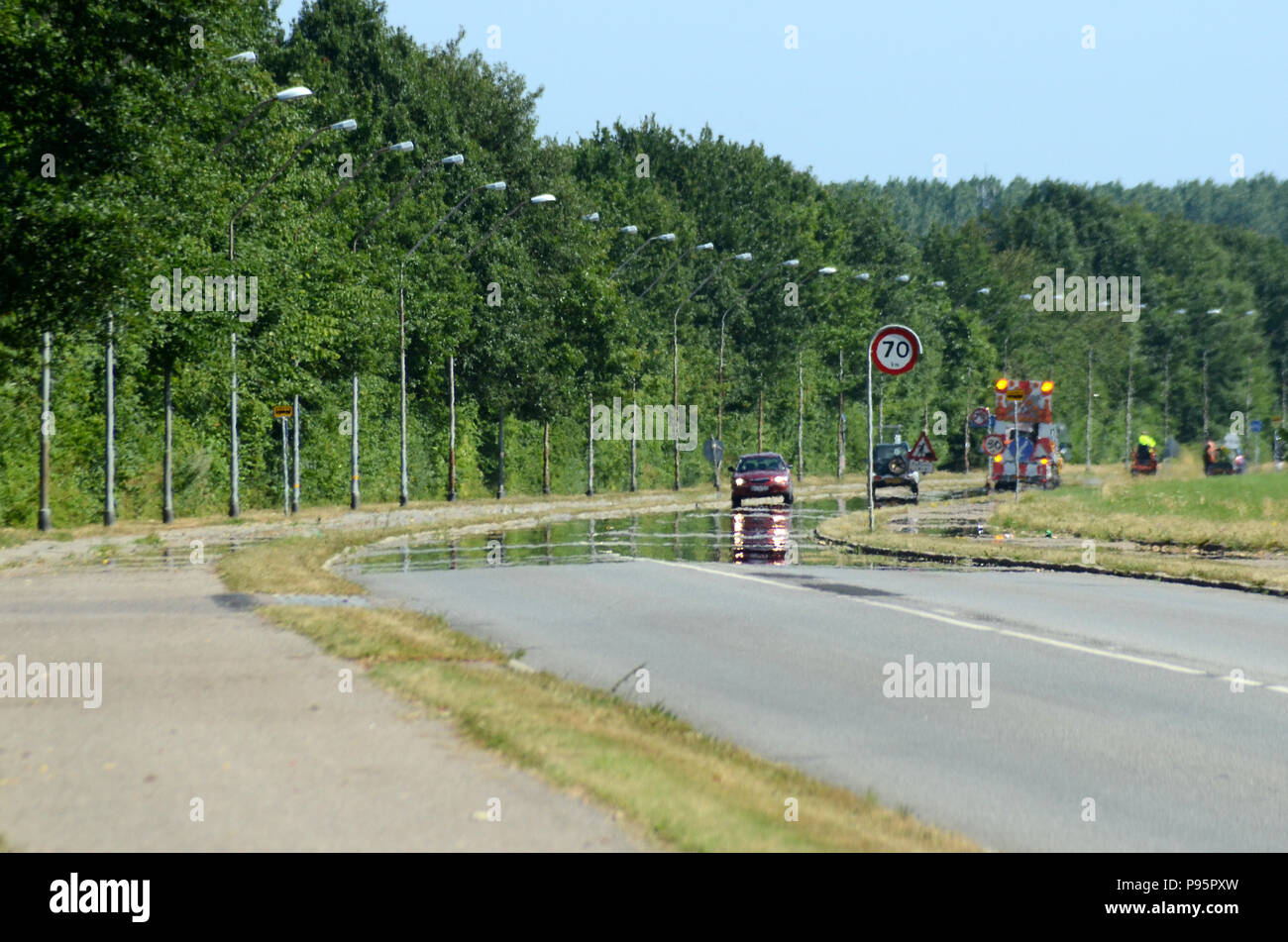 This road looks wet, but it is not, it is a mirage caused by a layer of hot air over the asphalt, heat distortion also obscuress the structures most f - Stock Image