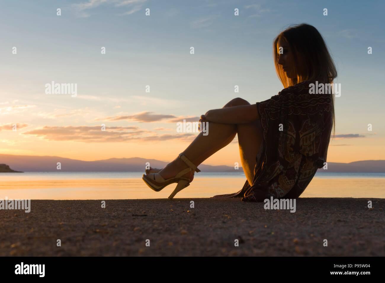 Heelsaddiced heelsaddict young woman person on seaside near sea in evening sunset time romantic serenity warm low light horizon island MR Stock Photo