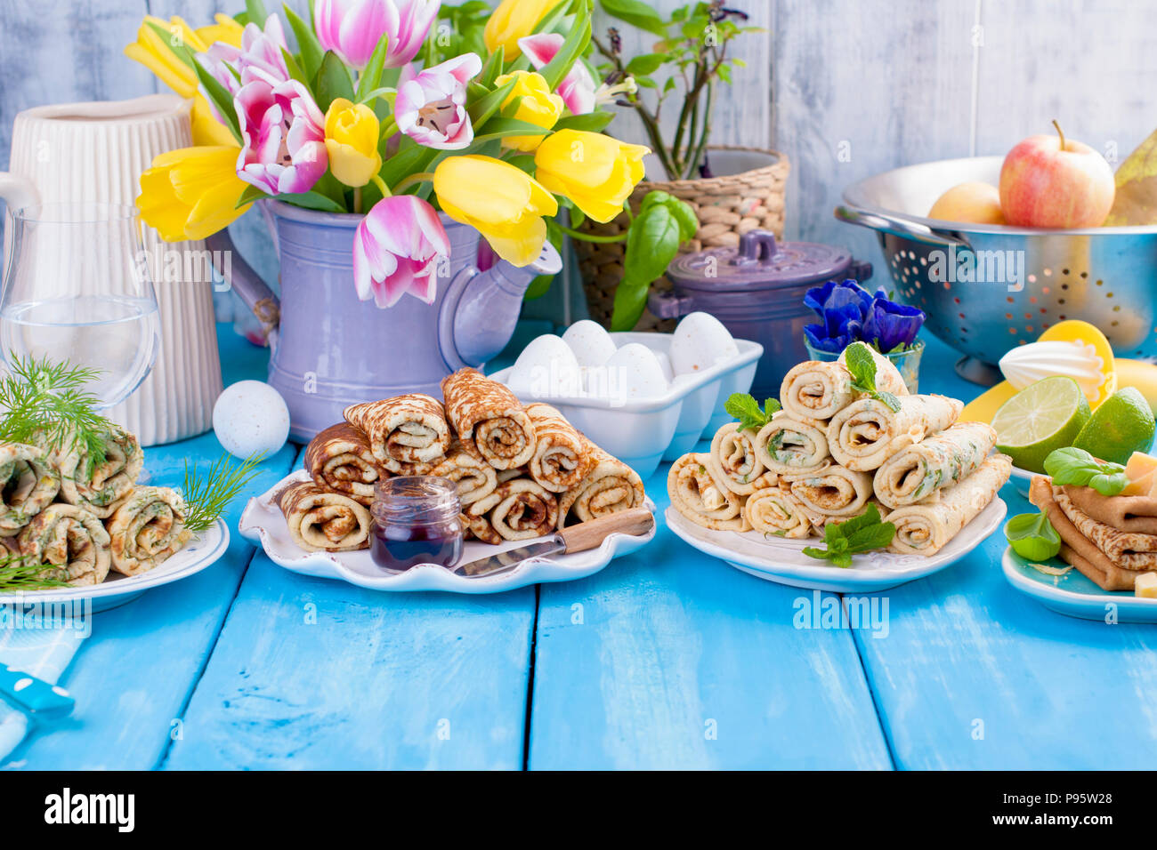 Many pancakes with different fillings and flavors. Delicious traditional Russian food in the spring. Homemade baking. Flowers and breakfast. Copy space - Stock Image