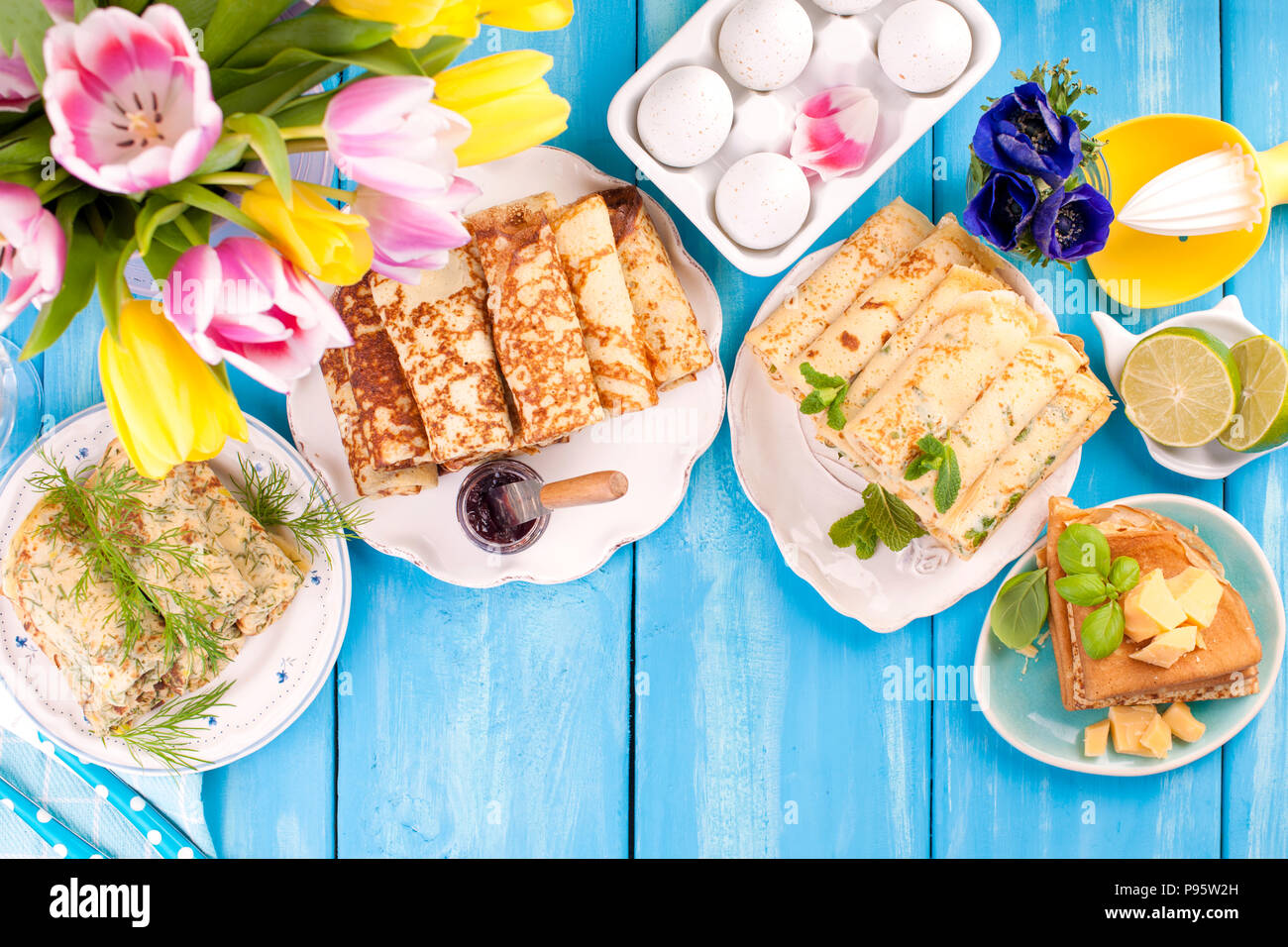 Many pancakes with different fillings and flavors. Delicious traditional food in the spring. Homemade baking. Flowers and breakfast. View from above. Copy space - Stock Image