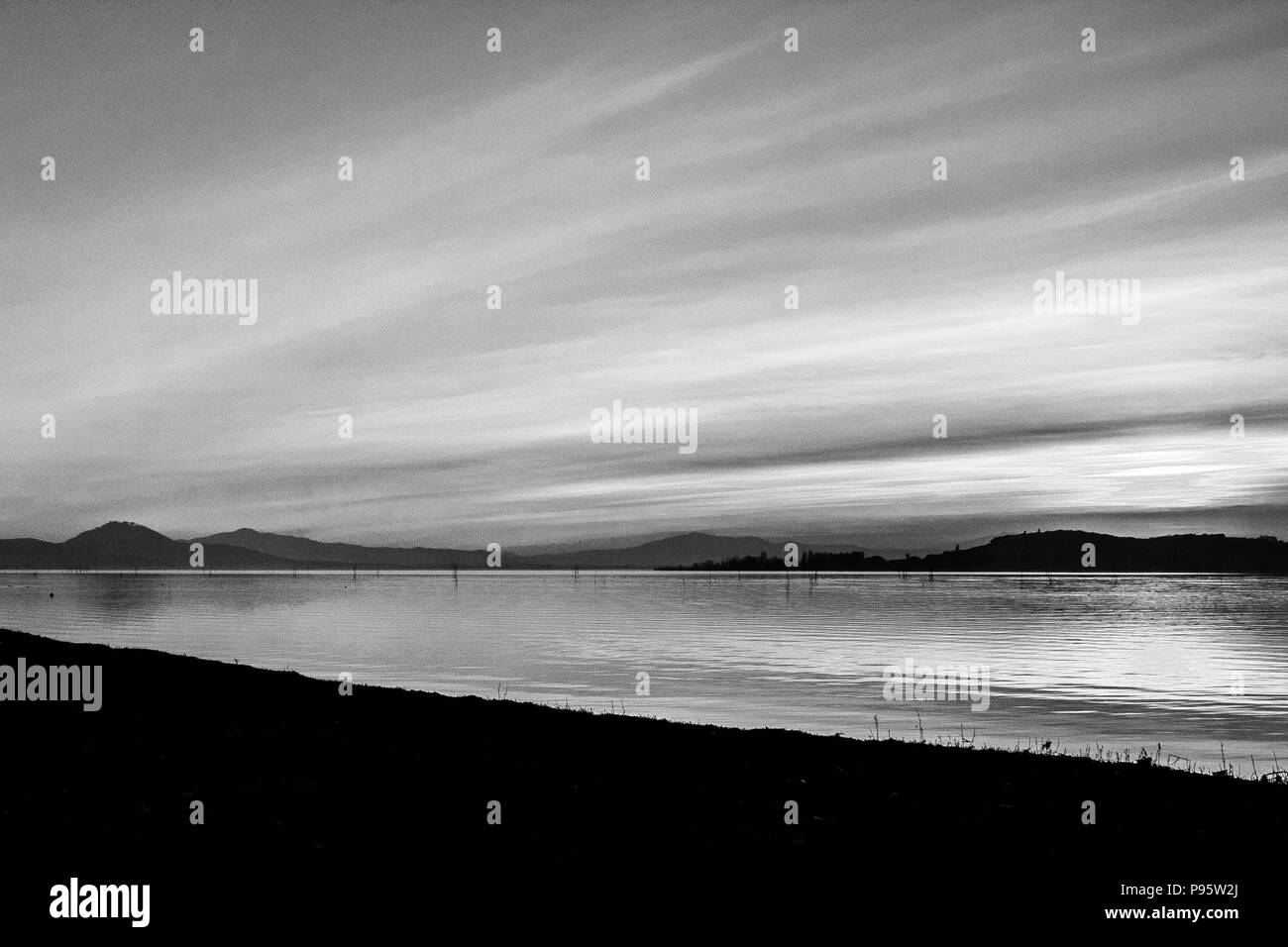 A shoot of a sunset over a lake, with sun coming down behind and island and many diagonal lines created by clouds and water waves - Stock Image