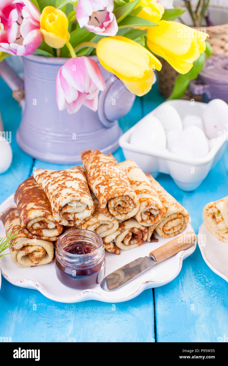 Homemade traditional pancakes with jam for spring carnival. Russian breakfast. Bright flowers of tulips. Blue background. Free space for text or a postcard. Copy space. - Stock Image