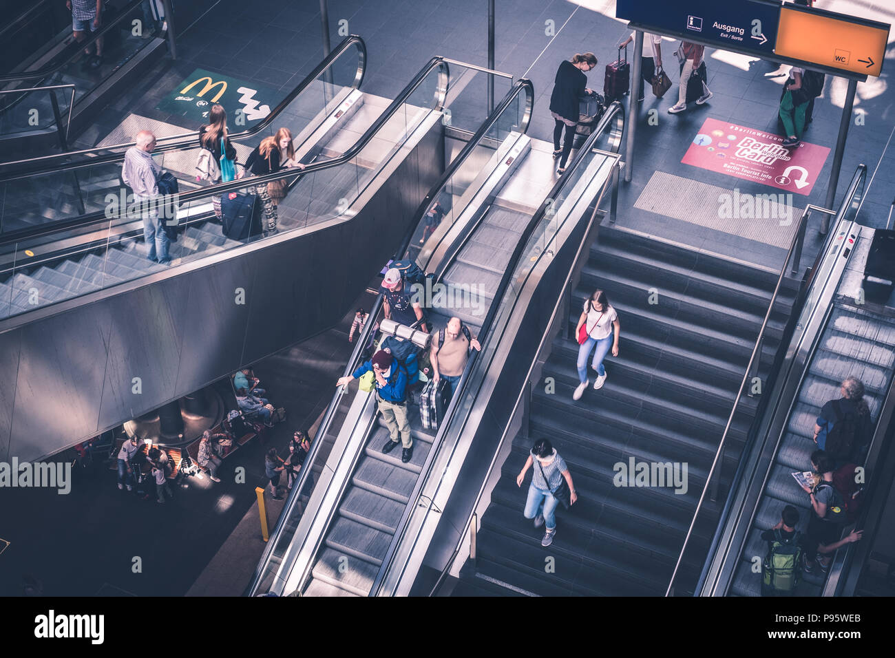 Berlin, Germany - july 2017: Traveling people with luggage on escalator inside main train station (Hauptbahnhof)   in Berlin, Germany - Stock Image