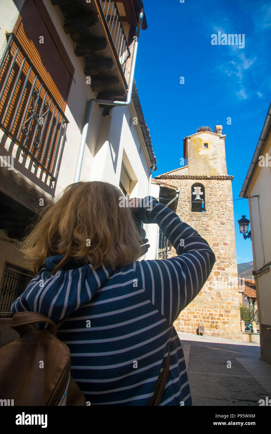 Woman taking photos of the church. Jerte, Caceres province, Extremadura, Spain. - Stock Image
