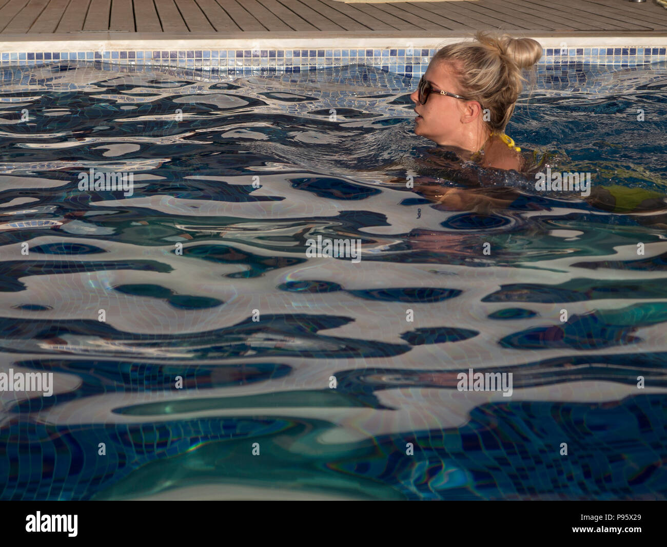 A beautiful girl in a yellow bikini swims lengths of a pool in the summer - Stock Image