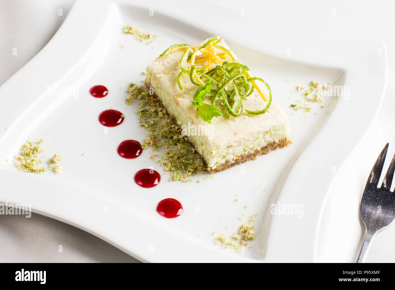 Raw food dessert cake with lemon and lime candied fruits on white plate - Stock Image