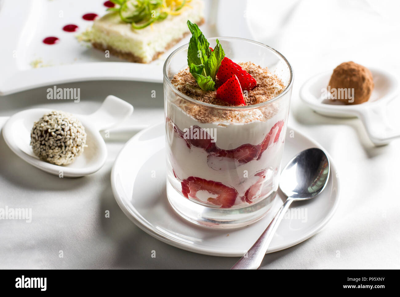 Sweet table with organic raw food desserts, sweets, yogurt with strawberries and cake - Stock Image