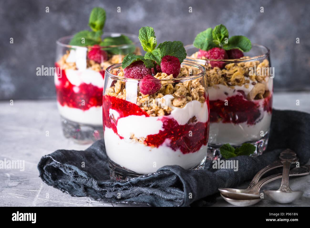 Healthy layered dessert with yogurt, granola, jam and raspberries in glass. - Stock Image