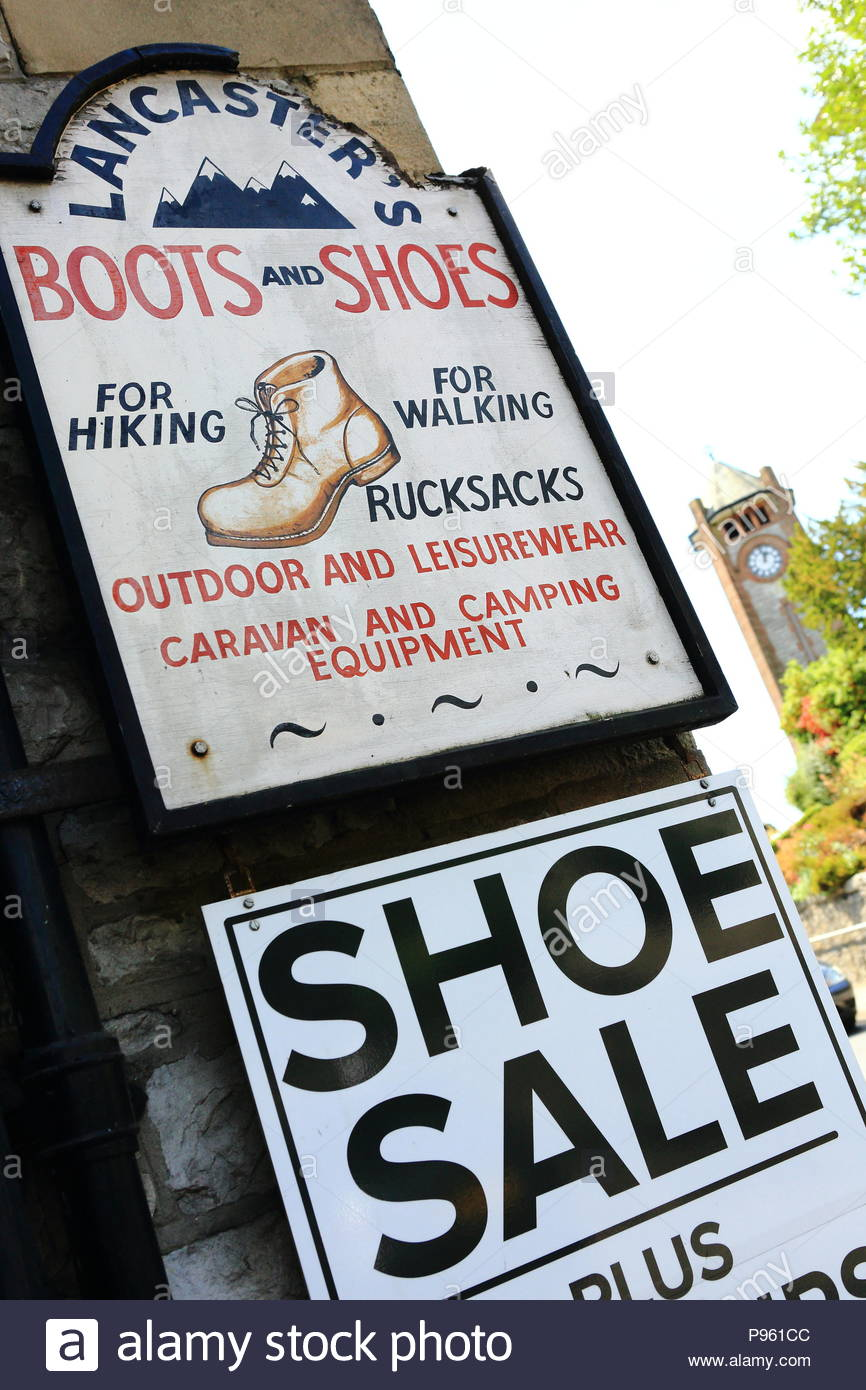 Boots & Shoe Sale sign on the shop front of the Lancaster Store at Cartmel, Grange-Over-Sands, Cumbria, England. Summer July 2018 - Stock Image