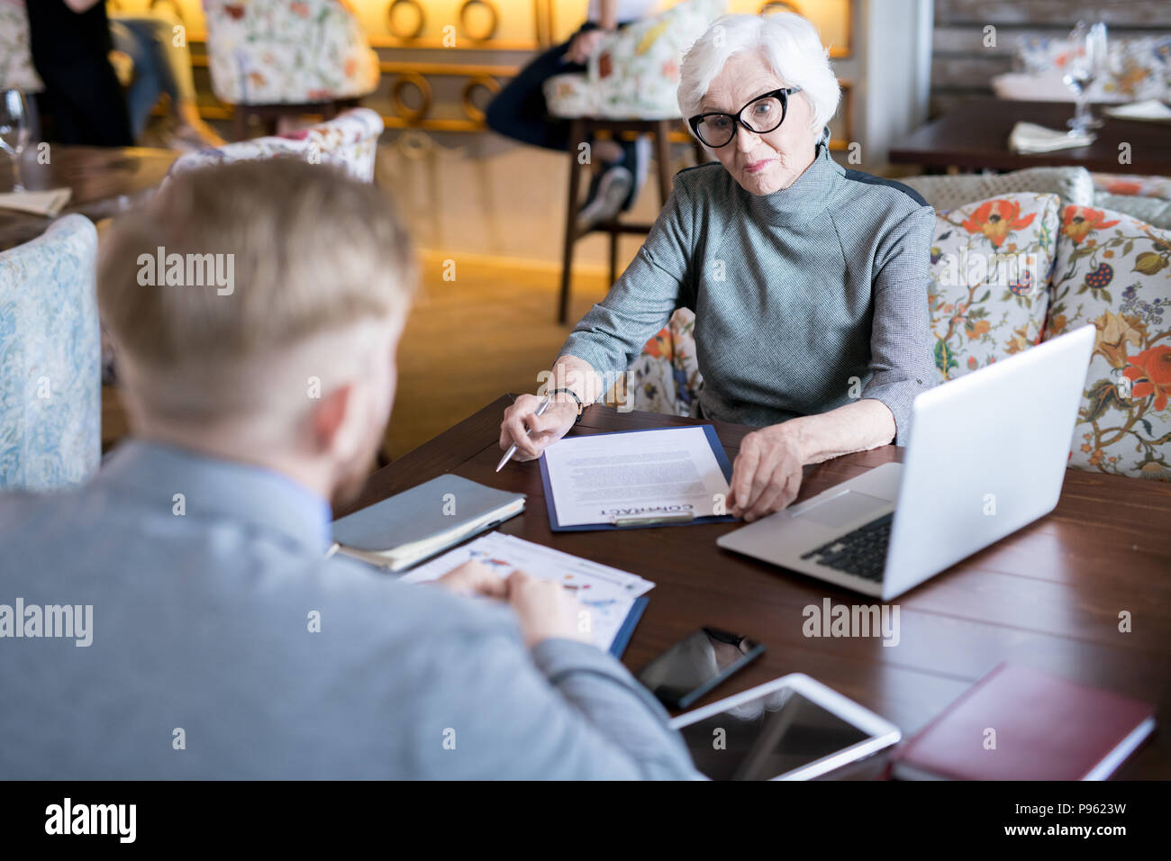 Senior businesswoman signing a contract - Stock Image