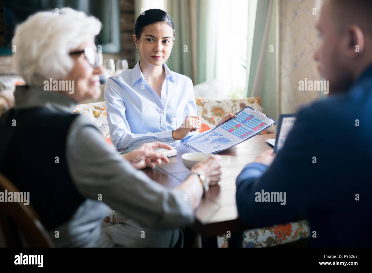 People discussing financial report - Stock Image