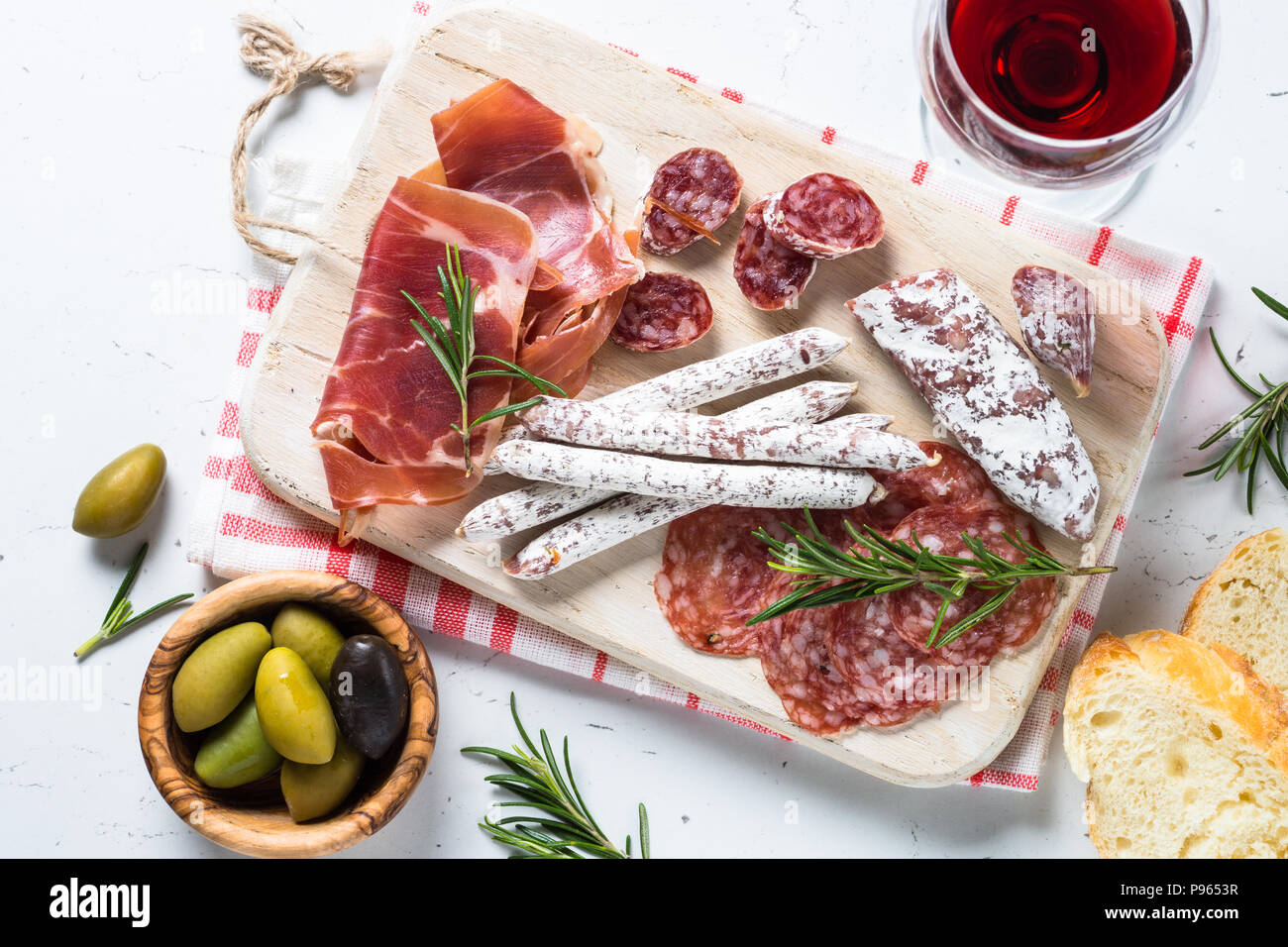 Antipasto. Traditional italian antipasto, sliced meat, appetizer on wooden cutting board on white table. Top view. - Stock Image