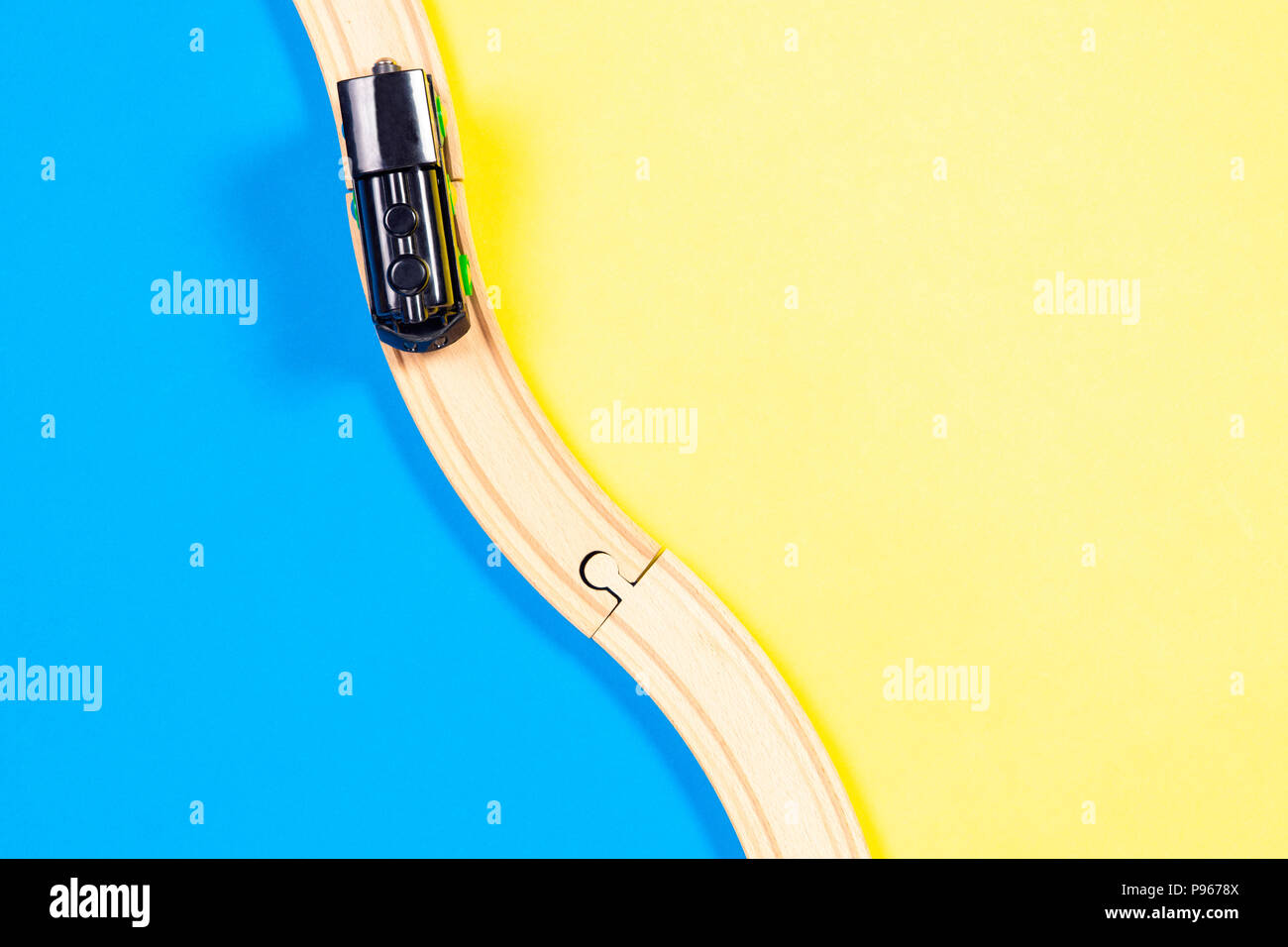 Toy train and curve wooden railways on colorful background - Stock Image
