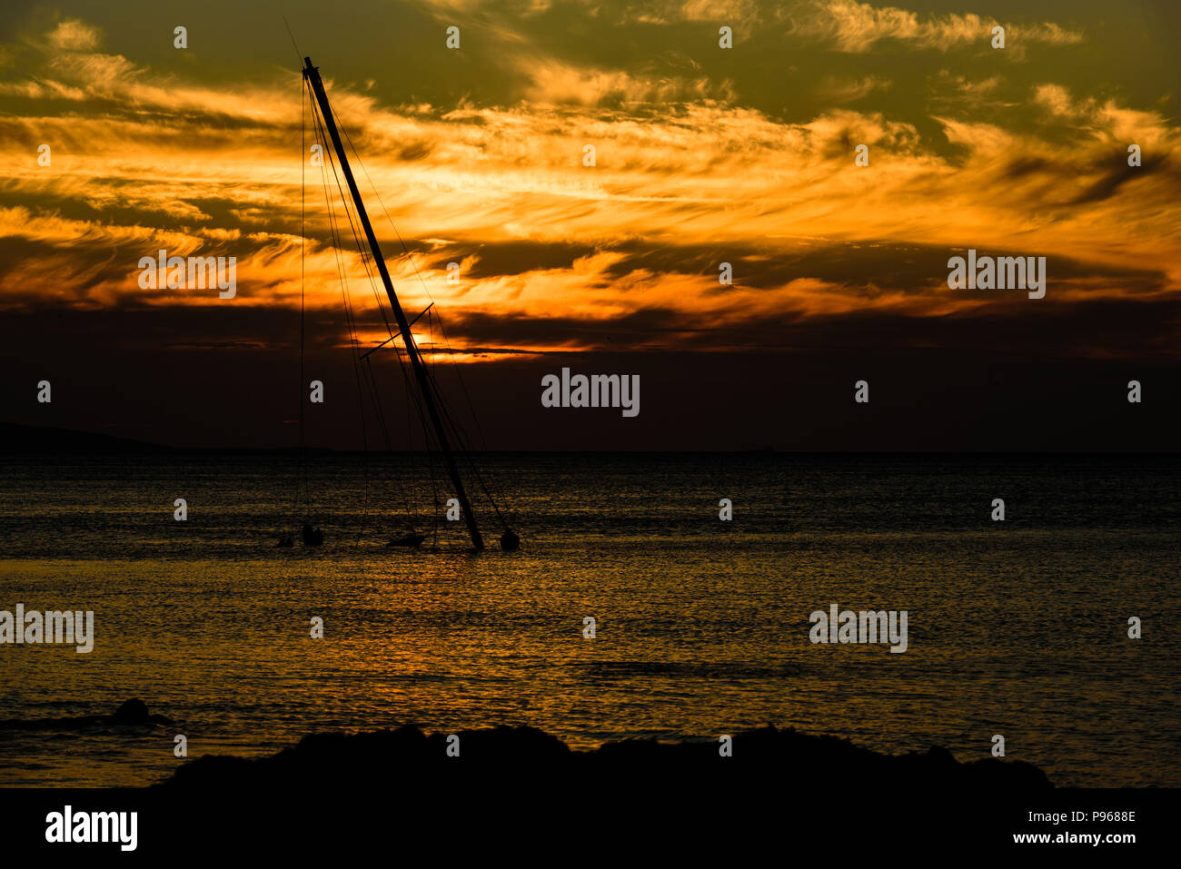 Sunset over a yacht sunk at Penmon lighthouse, Anglesey - Stock Image
