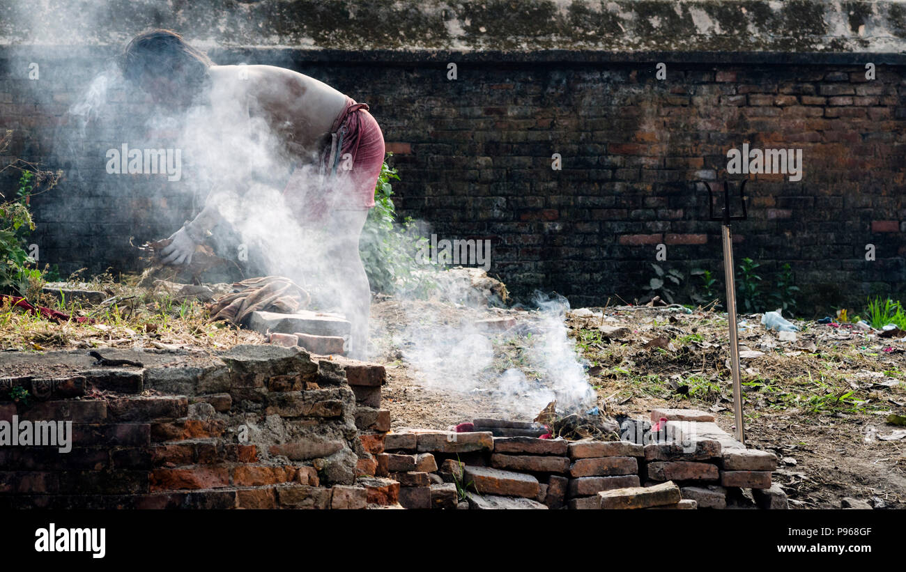 Sadhu preparing fire for ritual during the traditional Hindu festival Maha Shivaratri in the vicinity of Pashupatinath temple in Kathmandu, Nepal - Stock Image