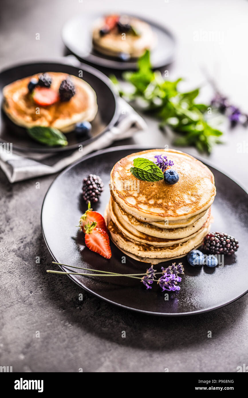 Pancakes with strawberries blackberries blueberries lavender and mint leaves. - Stock Image
