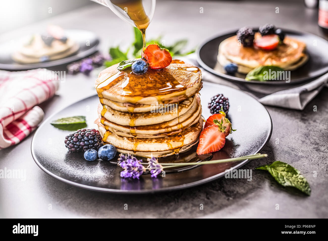 Pancakes with strawberries blackberries blueberries lavender mint leaves and maple syrup. - Stock Image