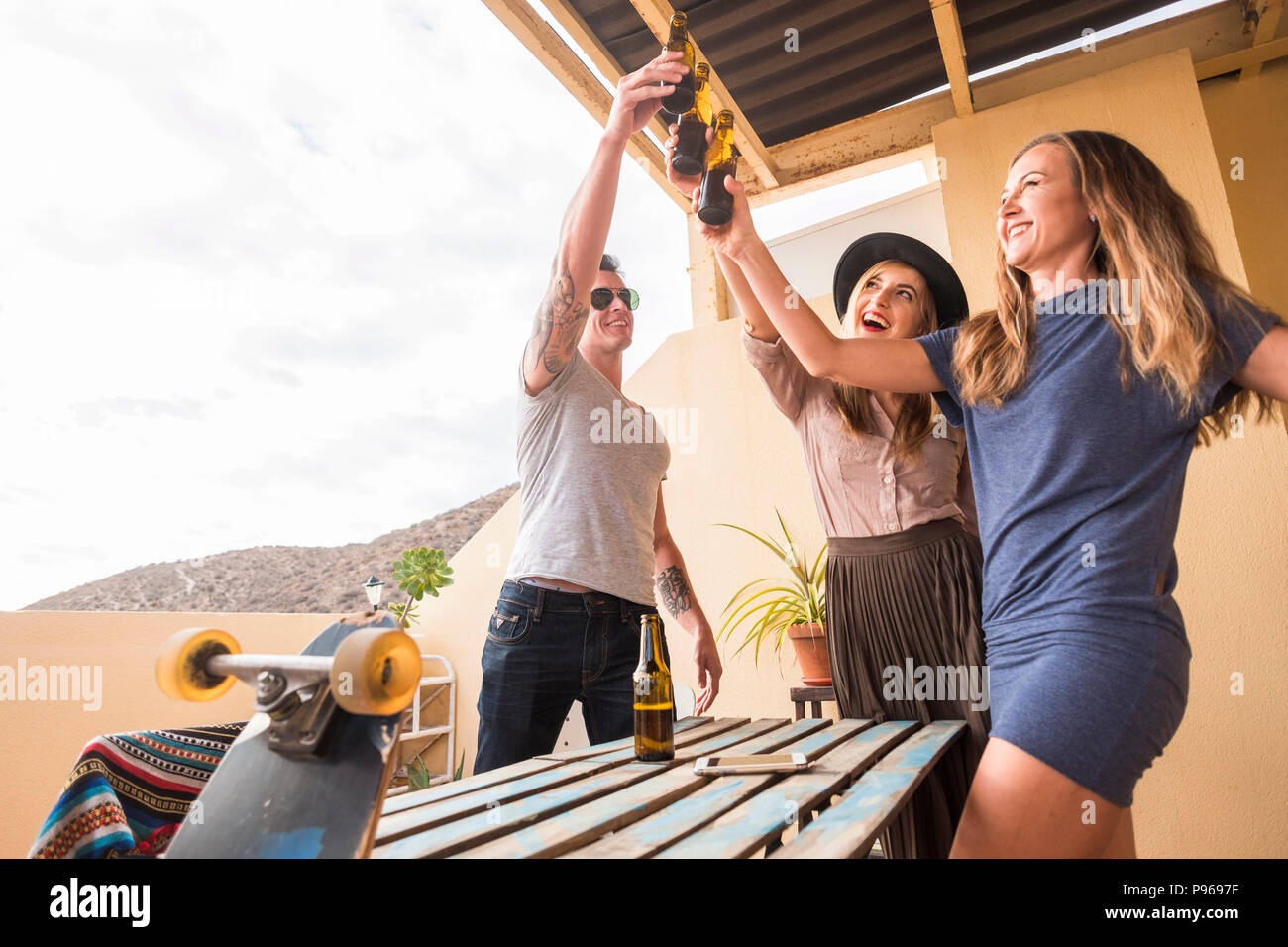 group of nice beautiful young people celebrate together with happiness on the terrace rooftop. drinking beers and having fun in a summer party style c Stock Photo