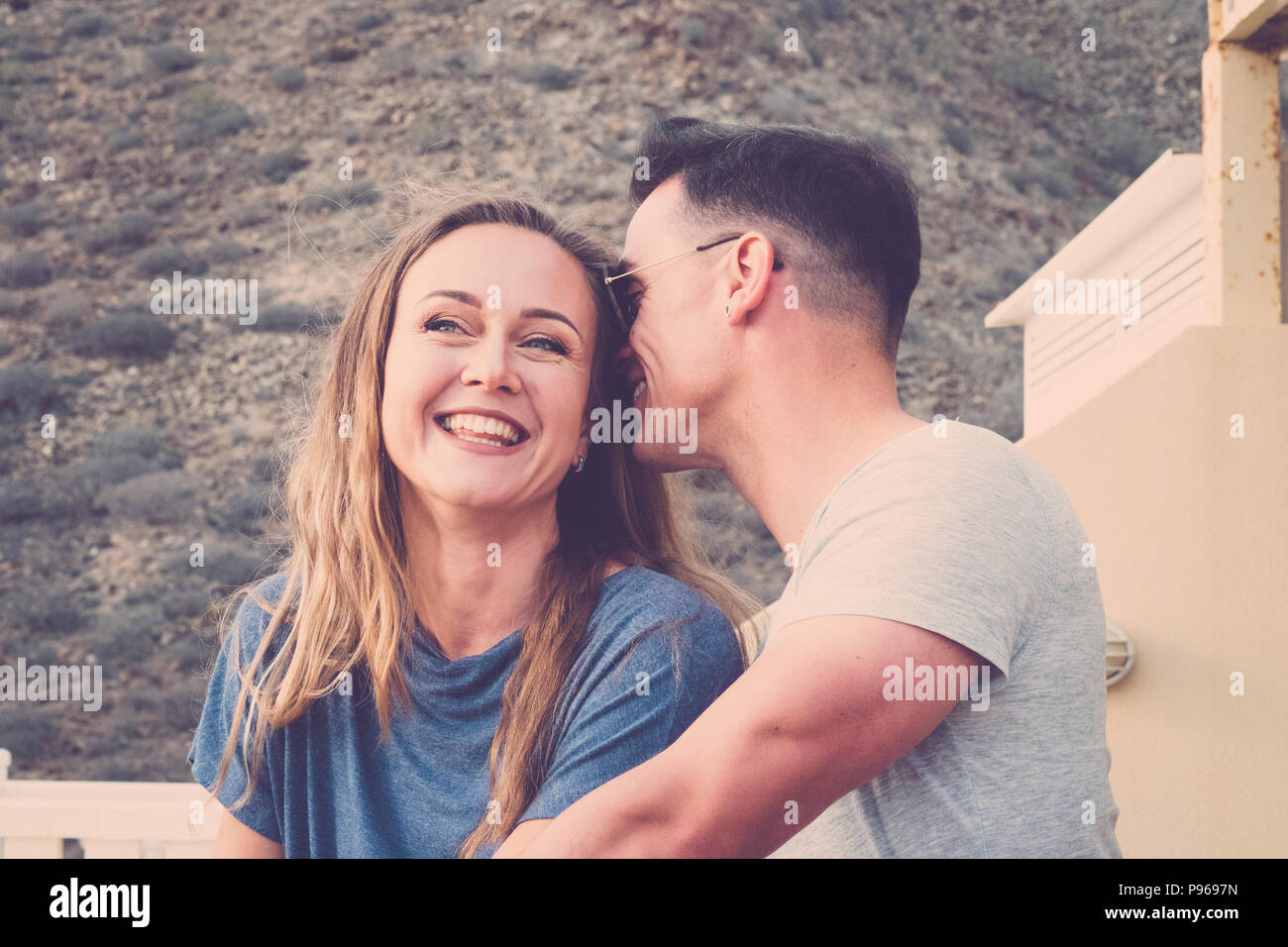 nice young couple caucasian in love together flirt and enjoy romantic time together on the terrace with mountain natural backgorund. happiness and rel - Stock Image