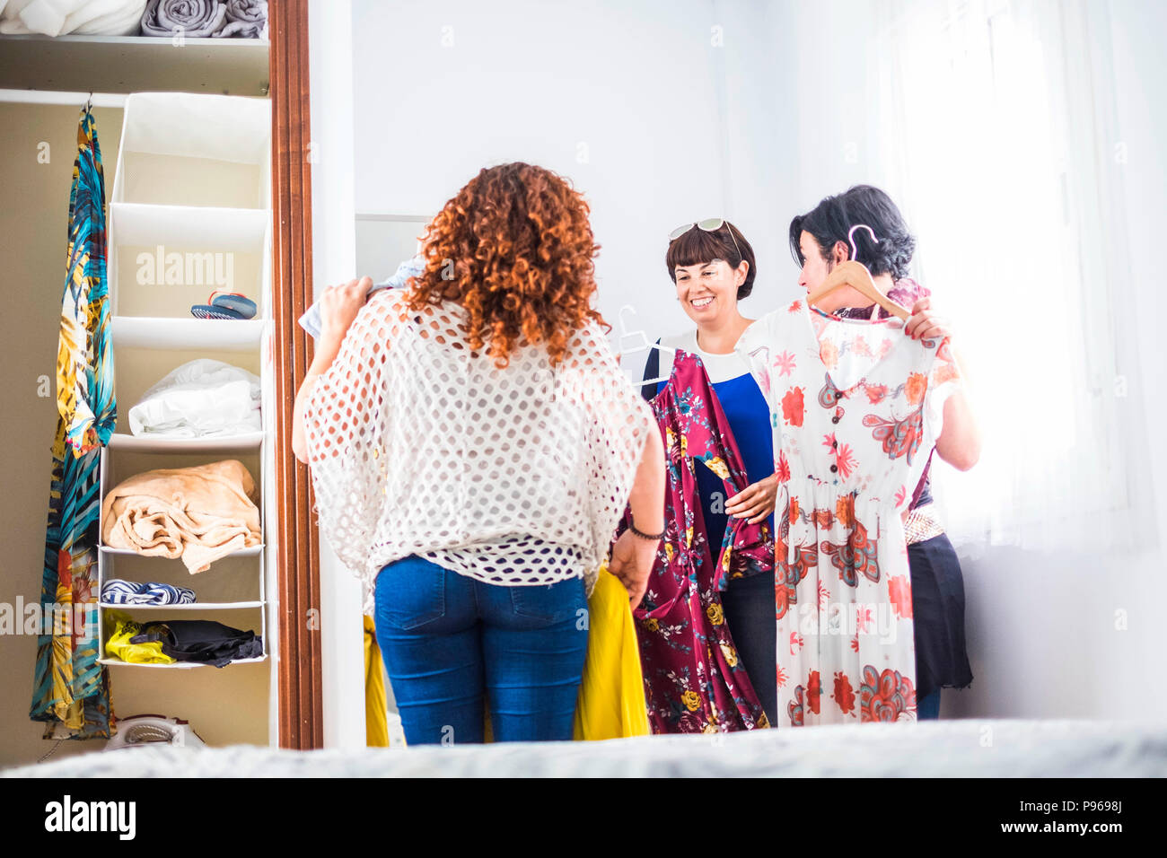 group of three caucasian young women at home choosing the dress ready for the night events and celebrate together in friendship. smiles and nice leisu - Stock Image