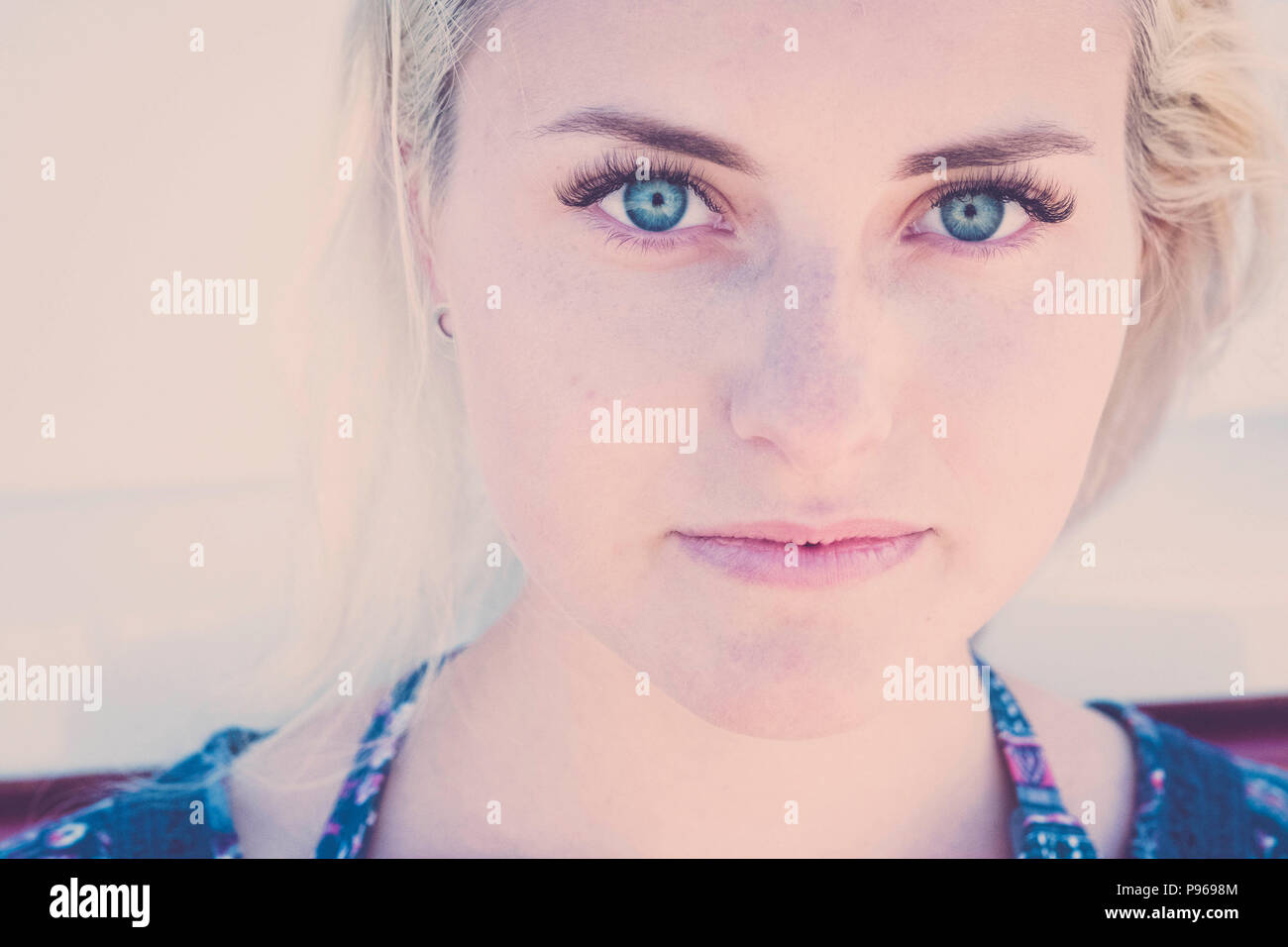 defocused portrait with focus on clear eye of a beautiful caucasian russina girl model young sit down and looking to you on camera. little smile relax - Stock Image
