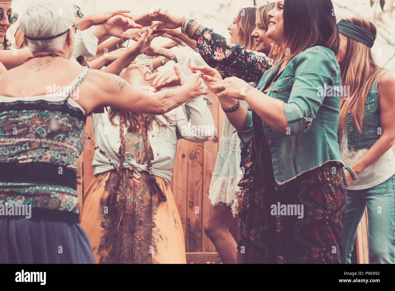 group of free and hippy rebel alternative style young women together dancing and celebrating with joy and happiness in a natural place indoor and outd - Stock Image