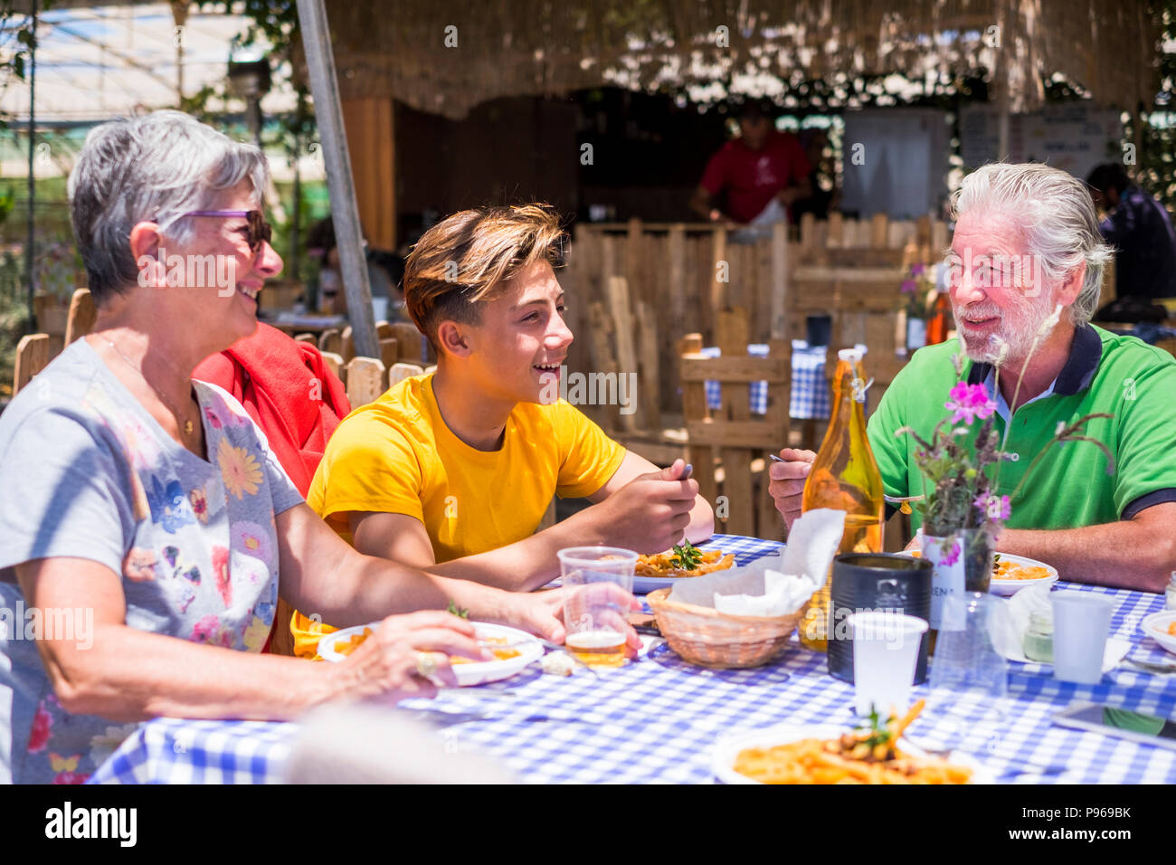 family caucasian people with grandmother grandfather grandson eating together in alternative natural place restaurant enjoying the meal and the vegeta - Stock Image