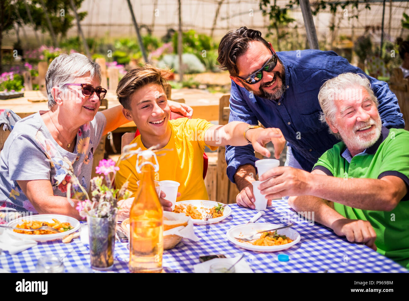 caucasian family enjoying the food in alternative natural restaurant. italian pasta. everybody smile and have fun together. grandfathers, son, grandso - Stock Image