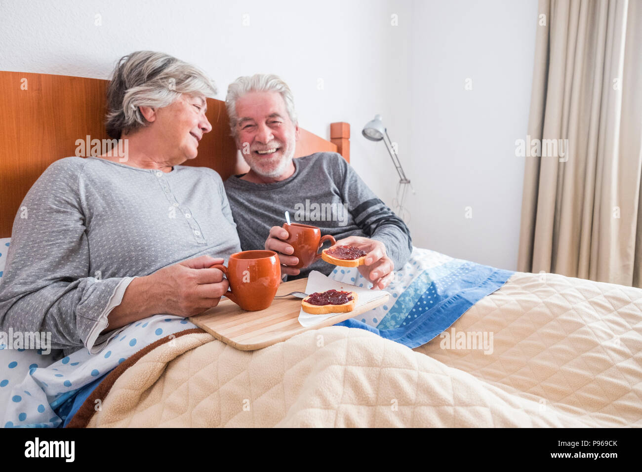 nice caucasian aged senior couple enjoying and laughing together waking up in the early morning. toasted and marmelade and coffee. togetherness and fo Stock Photo