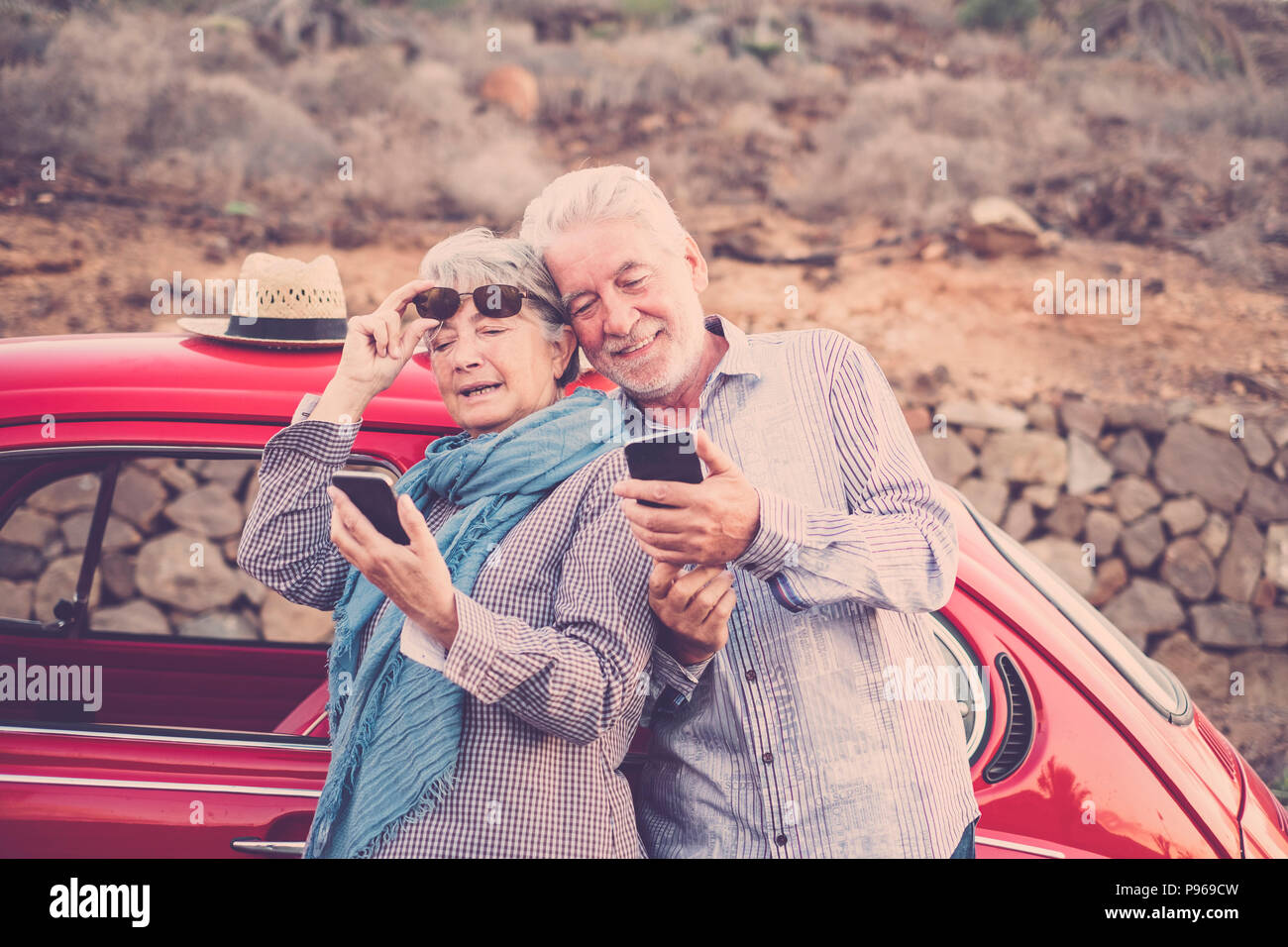senior adult couple check and look mobile phones to connect with internet or take a photo selfie. vintage red car ready to travel and everywhere in th - Stock Image