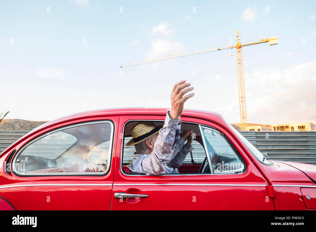 caucasian mature couple travel and drive on a red vintage car. vacation and wonderlust concpet for happy people moving around the world. home building - Stock Image