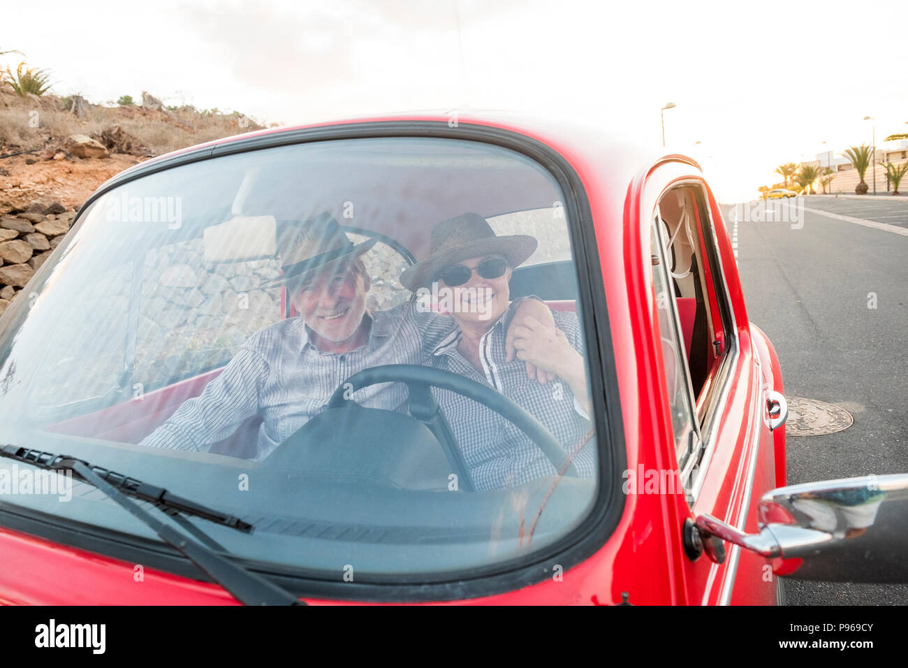 nice adult couple hug and love inside a red old vintage car parked on the road. smiles and have fun traveling together. happiness and lifestyle for ni - Stock Image
