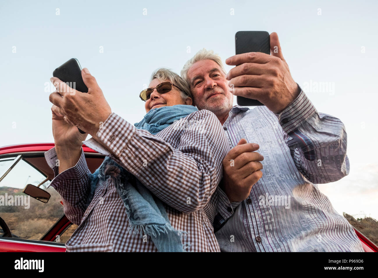 alternative point of view from the bottom for young senior couple caucasian people using smartphone to take pictures and connect to internet. travel a - Stock Image