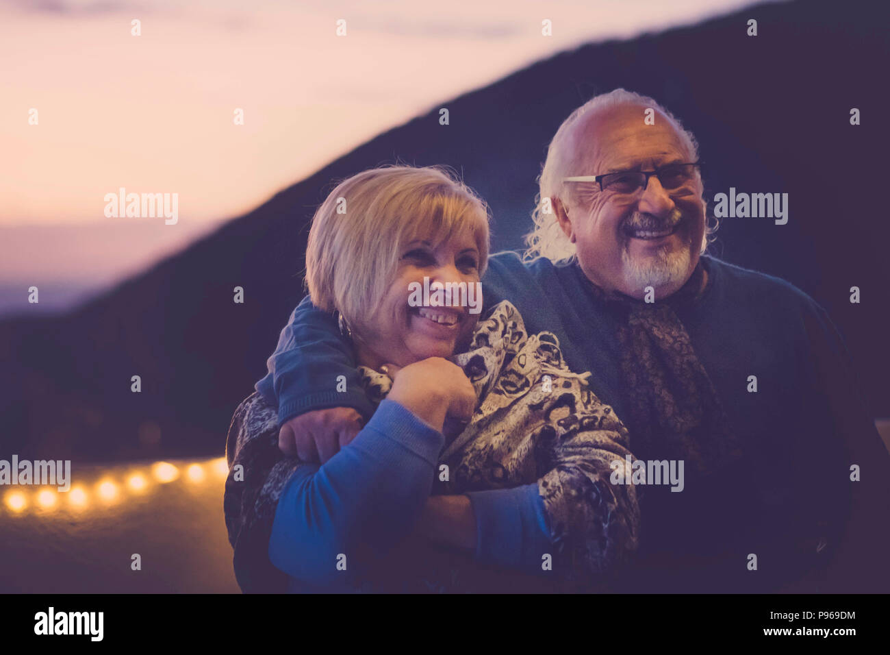 man and woman senior gentlemens aged in love hug and have fun smiling on the rooftop in vacation at home. night light atmosphere for romantic scene. t - Stock Image