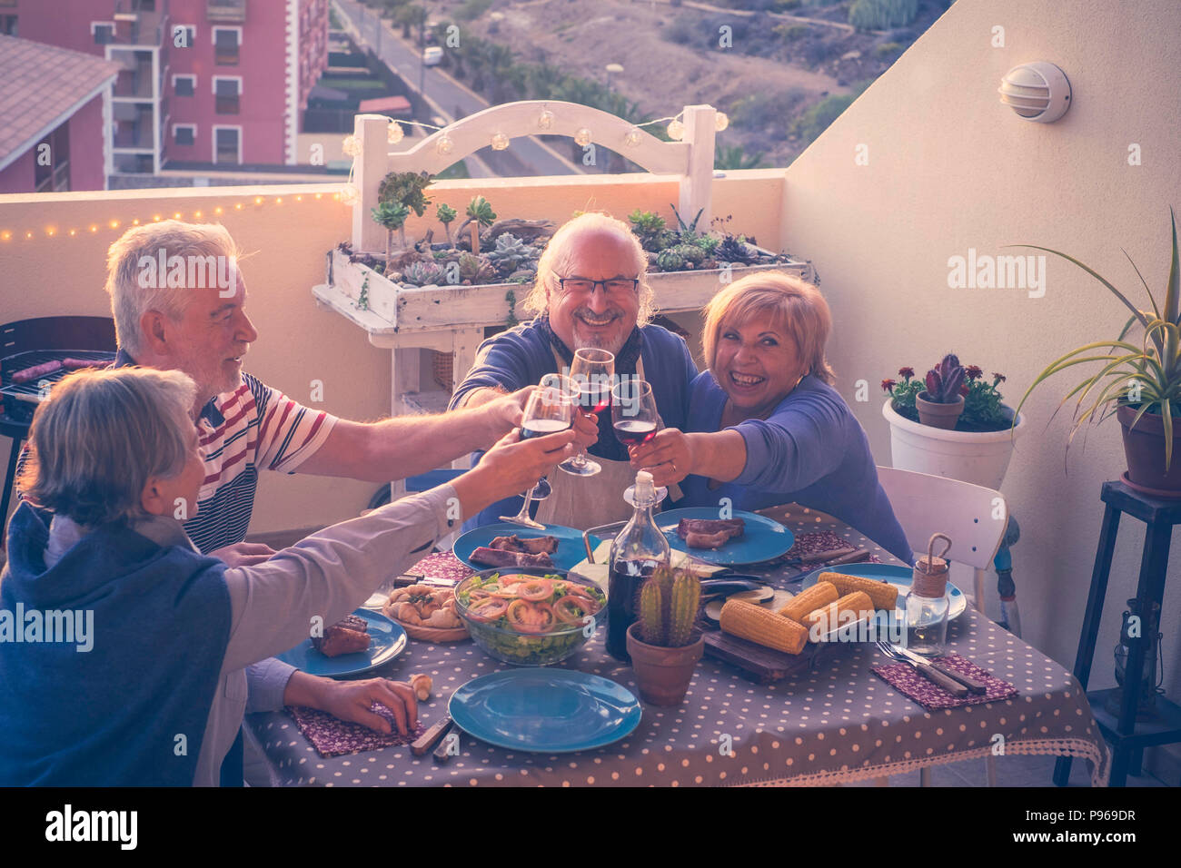 group of caucasian adult mature people eating and drinking together celebrating event by night on the rooftop with city and nature view. summer time a - Stock Image